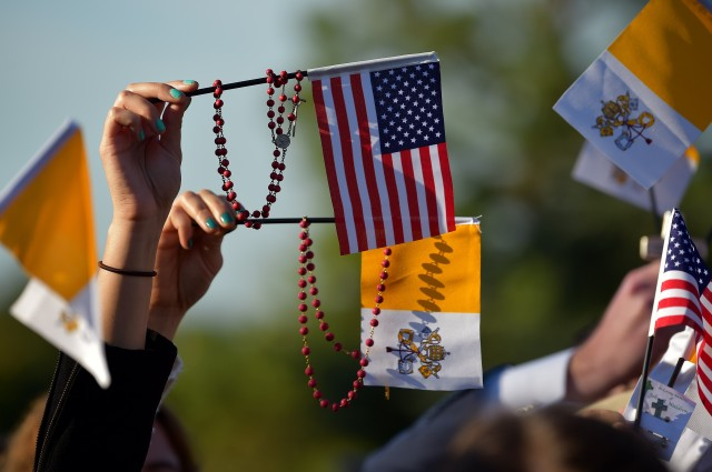 People wave US and Vatican flags as they wait for the arrival of the Pope Francis at the White House in Washington DC on September 22, 2015. A crowd of thousands are stretched back across the gloriously sun-kissed South Lawn awaiting the arrival of Pope Francis and President Barack Obama. AFP PHOTO / VINCENZO PINTO        (Photo credit should read VINCENZO PINTO/AFP/Getty Images)